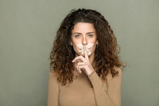Mulher com fita adesiva nos lábios mostrando gesto de silêncio