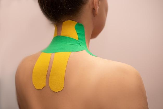 Mulher com fita de cinesioterapia nas costas