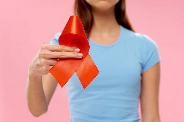Mulher com fita nas mãos, dia do câncer de mama, câncer de órgão feminino, dia do câncer