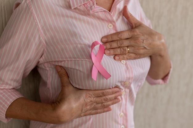 Mulher com fita rosa, segurando a mão no peito. autoexame das mamas. outubro rosa.