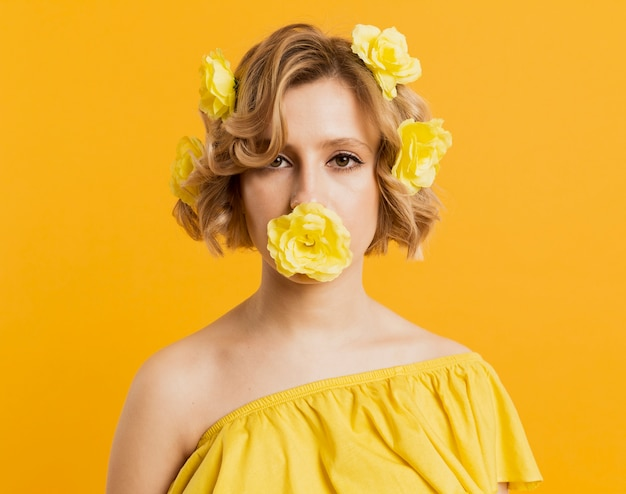 Mulher com flor cobrindo a boca
