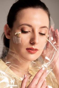 Mulher com flor de band-aid e plástico no rosto