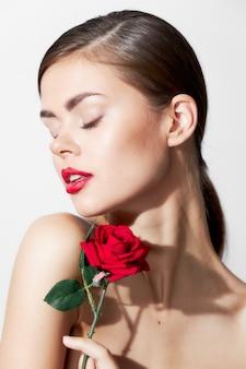 Mulher com flor olhos fechados rosa nas mãos de close-up de luxo charme