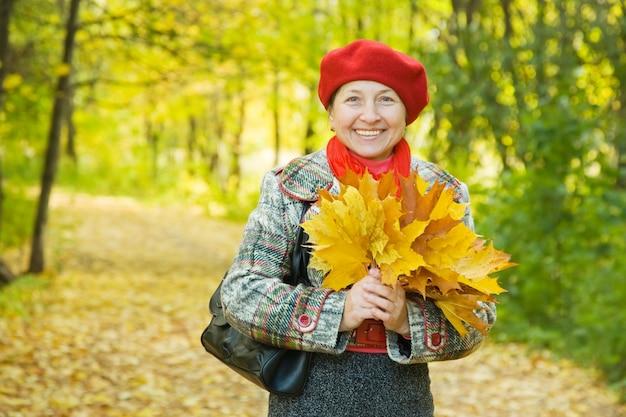 Mulher com folhas de bordo no parque de outono