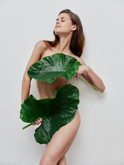 Mulher com folhas verdes cobrindo partes do corpo nuas com os olhos fechados
