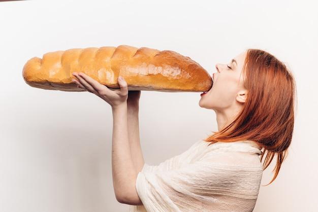Mulher com fome comendo grande pedaço de luz de vista lateral do naco de pão.