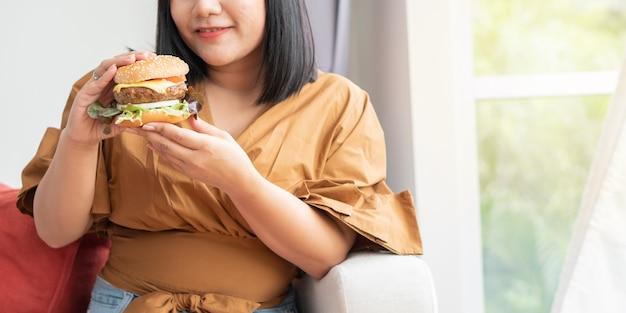 Mulher com fome segurando o hambúrguer e sentado na sala de estar