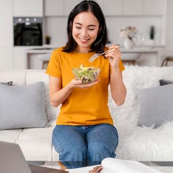 Mulher com fone de ouvido comendo durante a videochamada