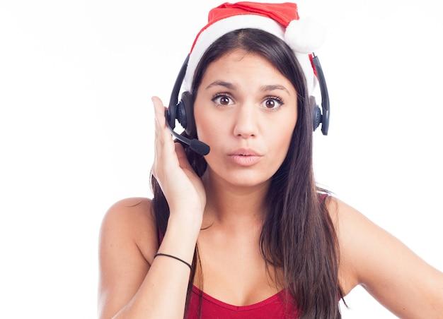 Mulher com fone de ouvido de natal da central de telemarketing usando chapéu de papai noel vermelho falando