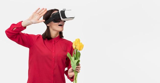 Mulher com fone de ouvido de realidade virtual segurando flores