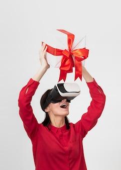 Mulher com fone de ouvido de realidade virtual segurando uma caixa de presente