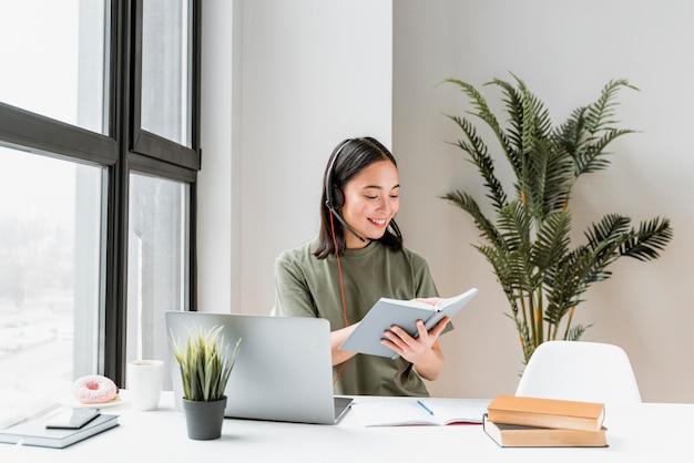 Mulher com fone de ouvido fazendo videochamada no laptop