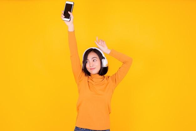 Mulher com fone de ouvido para ouvir músicas em fundo amarelo