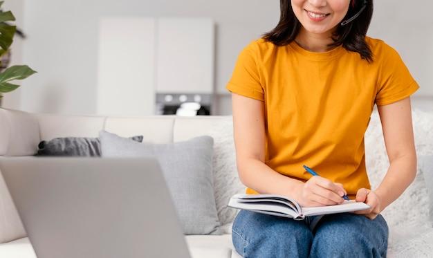 Mulher com fone de ouvido para videochamada no laptop