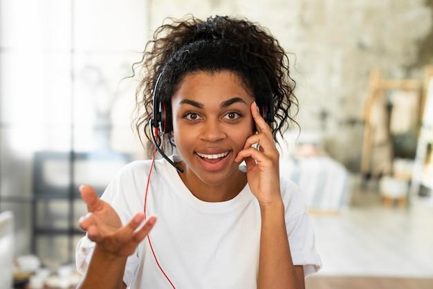 Mulher com fone de ouvido trabalhando em casa