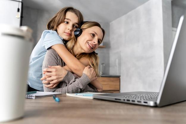 Mulher com fone de ouvido trabalhando em laptop abraçada por uma garota