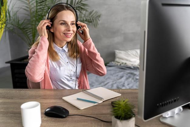 Mulher com fone de ouvido trabalhando no computador