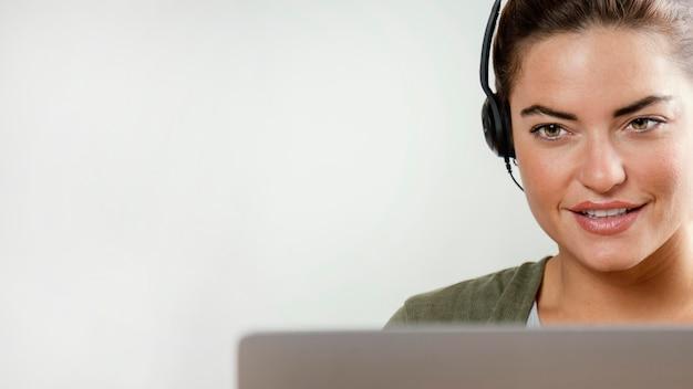 Mulher com fone de ouvido usando laptop