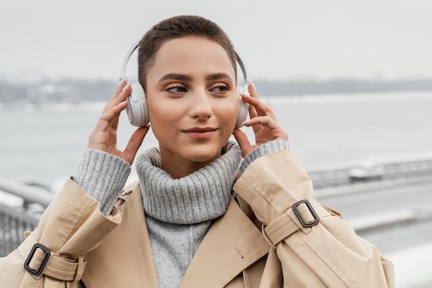 Mulher com fones de ouvido do lado de fora