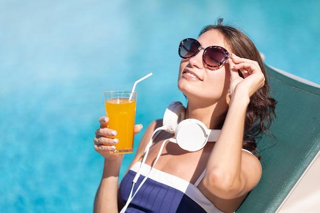 Mulher com fones de ouvido e bebida deitado no salão
