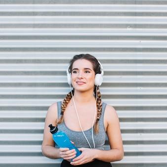 Mulher com fones de ouvido e bebida