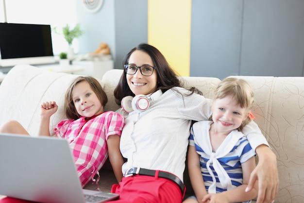 Mulher com fones de ouvido e laptop no colo abraçando crianças em casa