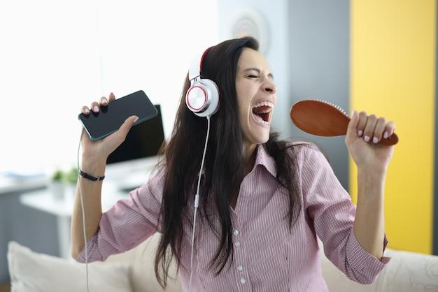 Mulher com fones de ouvido e pente nas mãos canta emocionalmente