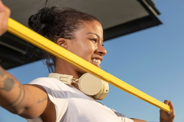 Mulher com fones de ouvido fazendo exercícios em casa
