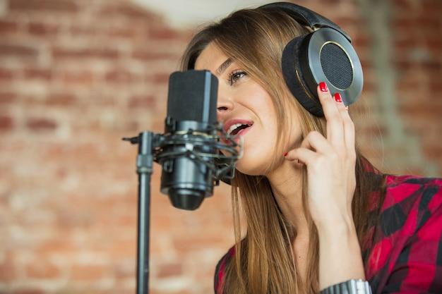 Mulher com fones de ouvido, gravando música, cantando ou fazendo um tutorial de transmissão de internet em pé no local de trabalho ou em casa.
