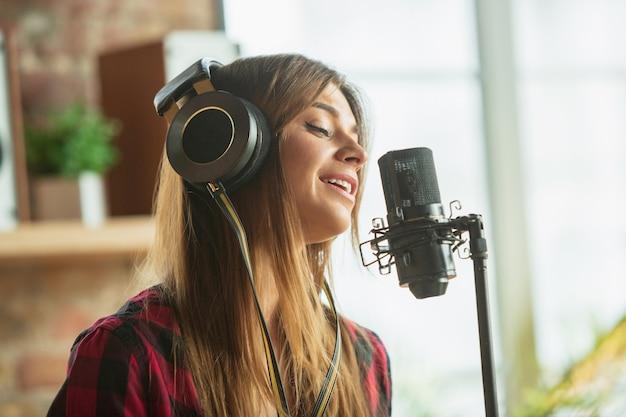 Mulher com fones de ouvido gravando música