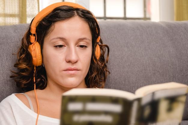 Mulher com fones de ouvido lendo um livro na sala, sentada no sofá