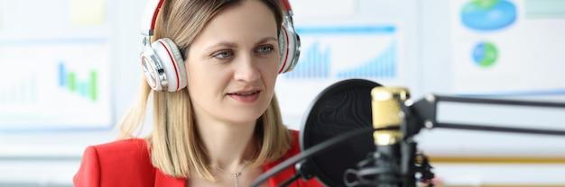 Mulher com fones de ouvido na frente do microfone em uma conferência de negócios on-line de mesa de trabalho