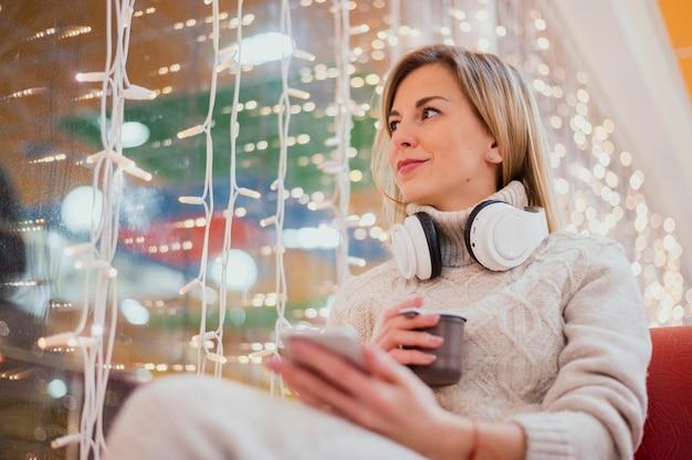 Mulher com fones de ouvido no pescoço e copo perto de luzes de natal