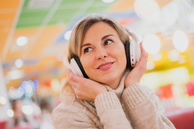 Mulher com fones de ouvido no pescoço, olhando para longe perto de luzes de natal