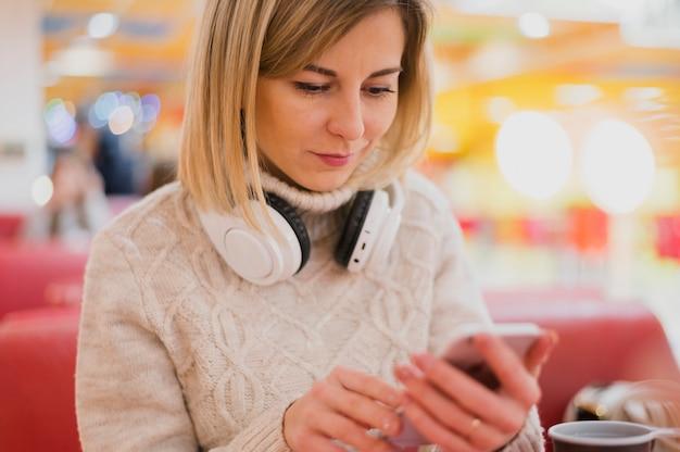 Mulher com fones de ouvido no pescoço, olhando para o telefone perto de luzes de natal