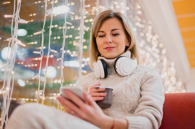 Mulher com fones de ouvido no pescoço perto de luzes de natal