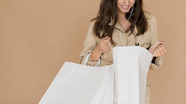 Mulher com fones de ouvido olhando nas sacolas de compras