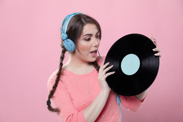 Mulher com fones de ouvido, olhando para o disco de vinil