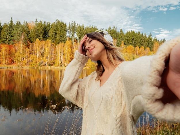 Mulher com fones de ouvido perto do lago no outono