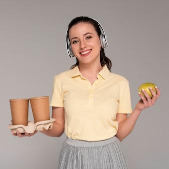 Mulher com fones de ouvido segurando copos de desenho animado e maçã
