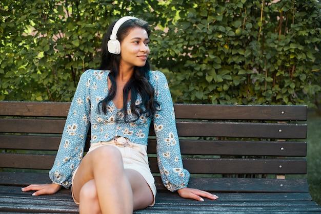 Mulher com fones de ouvido, sentado em um banco