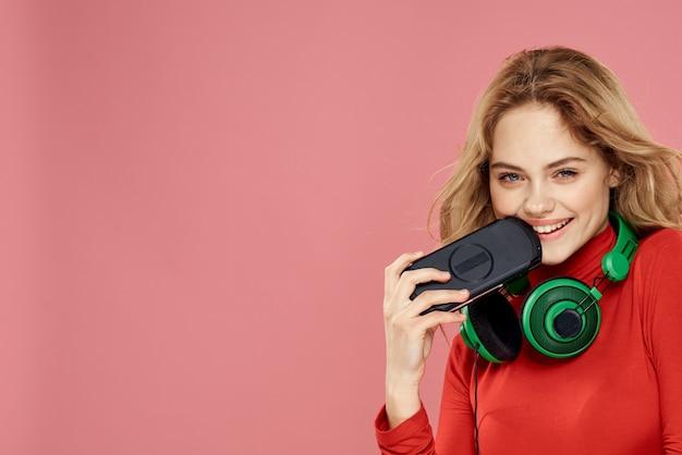 Mulher com fones de ouvido set-top box móveis jogando jaqueta vermelha de parede rosa estilo de vida.