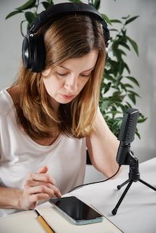 Mulher com fones de ouvido tem aulas on-line em casa e-learning e conceito de podcast