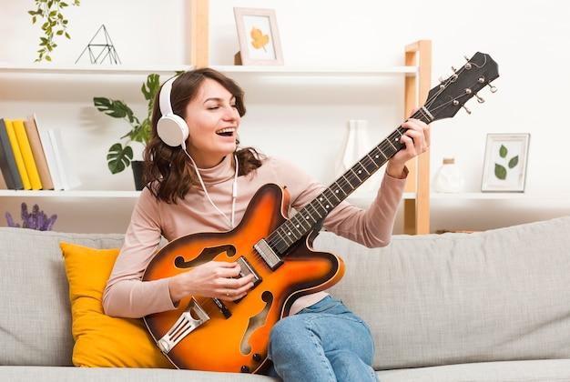 Mulher com fones de ouvido tocando violão