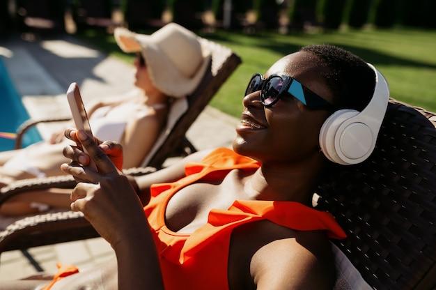 Mulher com fones de ouvido tomando banho de sol na espreguiçadeira na piscina