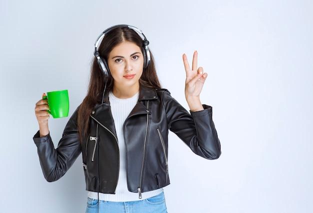 Mulher com fones de ouvido, tomando uma xícara de chá verde.