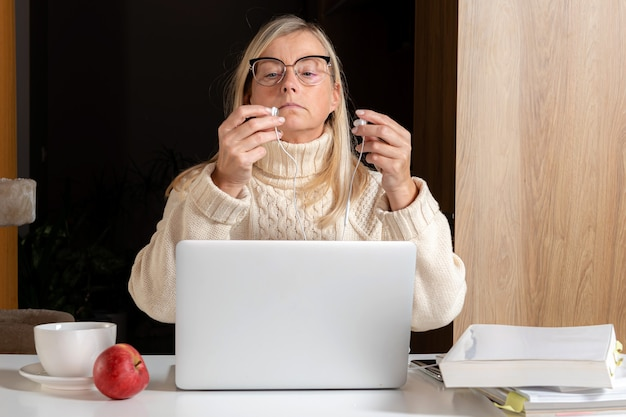 Mulher com fones de ouvido usando o celular enquanto trabalha com o laptop na cozinha de casa, trabalhando online.