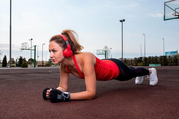 Mulher com fones de ouvido vermelhos fazendo exercícios abdominais na terra no parque.