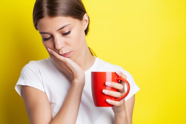 Mulher com forte dor de dente, segurando a mão sobre a bochecha.