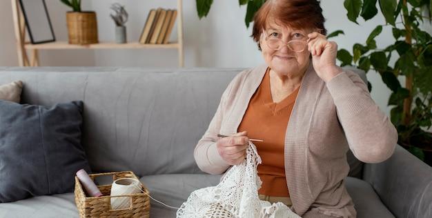 Mulher com foto média fazendo crochê dentro de casa